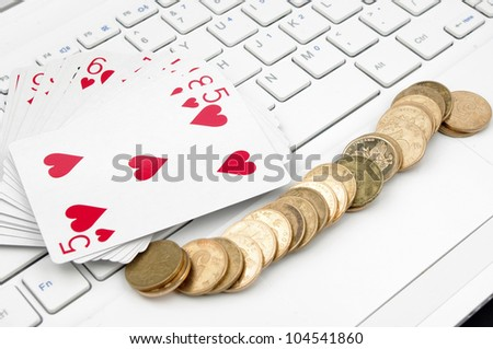 Poker, money and computer keyboard (the expression of an online poker game, or against the concept of online gambling) - stock photo