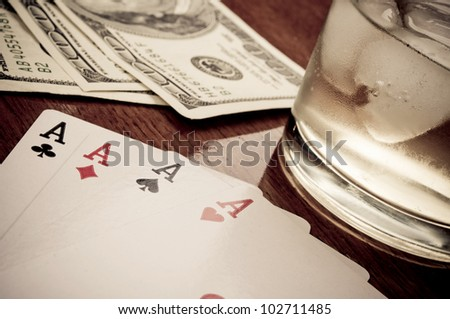 Poker of aces on the wooden table, whiskey with ice cubes and hundred-dollar bills in the background