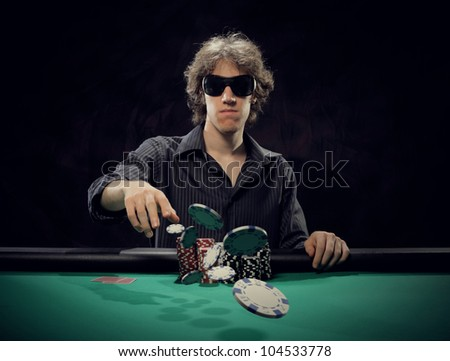 Poker player at a poker table throwing his chips