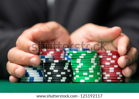 "Poker player going ""all in"" pushing his chips forward. Addiction to the gambling"