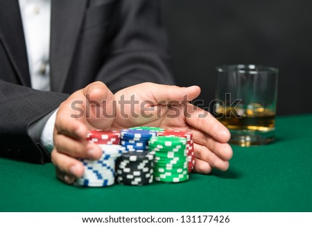 "Poker player going ""all in"" pushing his poker chips forward. Risky entertainment of gambling"