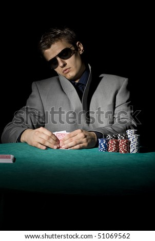 Poker player looking at his cards - stock photo