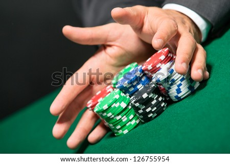 """Poker player stakes """"all in"""" pushing his chips forward. Risky entertainment of gambling"""