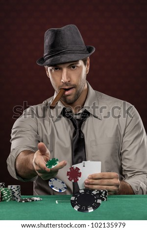 Poker player wearing hat and smoking a cigar, on a red background, throwing poker chips.