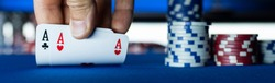 Poker tournament at casino: a player is holding two ace cards