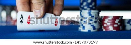 Poker tournament at casino: a player is holding two ace cards #1437073199