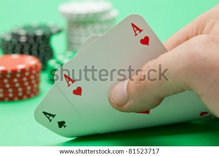 Pokerplayer shows pocket aces with poker chips in the back over green background