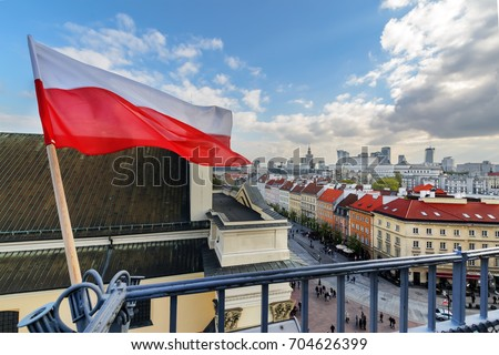 Poland Flag in Blue Sky and the centre of Warsaw in background #704626399