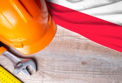 Poland flag with different construction tools on wood background, with copy space for text. Happy Labor day concept.