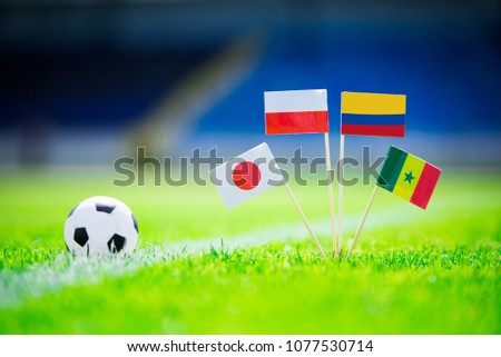 Poland, Senegal, Columbia, Japan national Flag and football ball on green grass. Fans, support photo, edit space. #1077530714