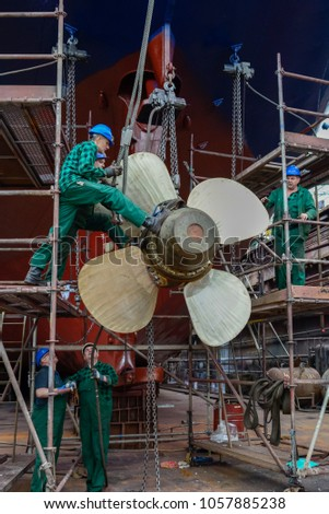 Poland, Szczecin - May 27, 2016: Workers install ship's propeller in dry dock on ship repairing yard #1057885238