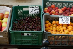 Poland, Warsaw, July 2021. Fruits and vegetables displayed in front of the store on the street are tempting with views, written prices.