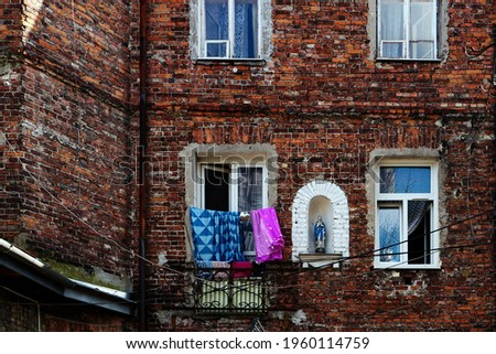 Poland, Warsaw, Praga Północ, April 2021. One of the tenement houses in Prague with the image of the Virgin Mary. A red brick building, washed linen hanging in the window. Zdjęcia stock ©
