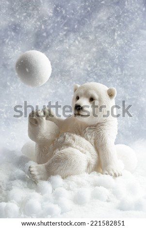 Polar bear winter decoration playing with a snowball