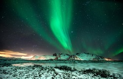 polar lights also called northern lights or aurora borealis in northern norway during winter above a fjord and snow covered mountains