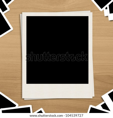 Polaroid blank photo frame on brown wooden background