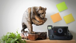 Polaroid Camera With Bear Wooden Sculpture on Table, Empty Space For Text