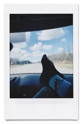 Polaroid of feet on dashboard of car on highway