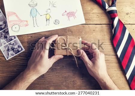 Polaroid pictures of father and daughter, childs drawing, present and tie laid on wooden desk backround.