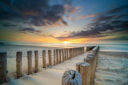 Pole heads or wave-breakers close-up disappearing in North Sea in Holland with sunset background of the sea and cloudy sky