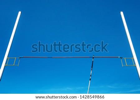 pole vault equipment: bar, pole and pole vault standards in background blue sky