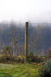 Pole with hurricane fence early in the morning. Autumn scenery with fog and hoar frost.