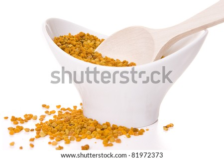 Polen bee inside a cup with a wood spoon isolated on white - stock photo