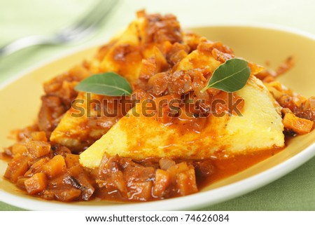 Polenta with carrot and onion on the white plate