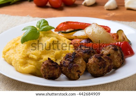 polenta with meatballs and fried vegetables on a white plate Stock fotó ©