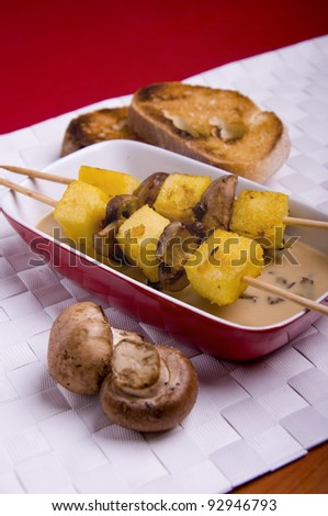 Polenta with mushrooms brochettes with toasted bread on a white mat