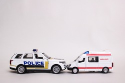 Police and ambulance toy car on gray background close up