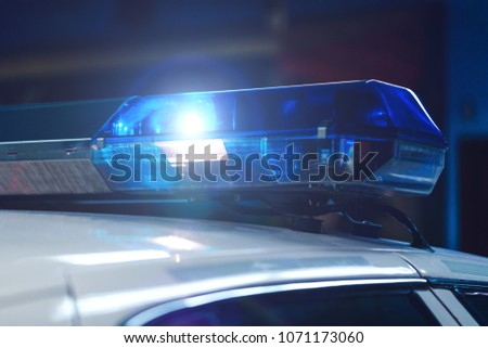 Police at night in the car with blue siren flasher. Siren on police car flashing, close-up. Police light and siren on the car in action. Emergency flashing police siren during night period.