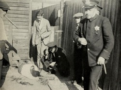 Police at the murder scene of an African American man during 1919 Chicago Race Riot. The victim was chased by a group of white men who stoned him to death as he attempted to find shelter in his home.
