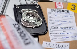 Police badge next to evidence bag, concept image