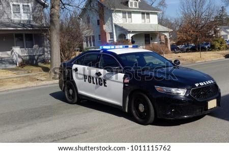 Police car barricade on residential neighborhood street.