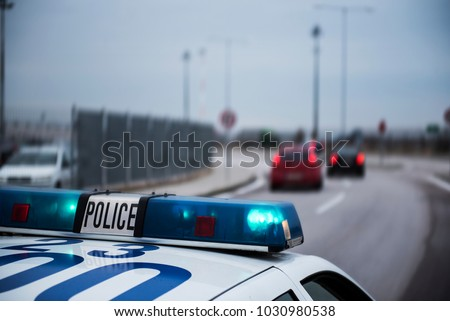 Police car following cars inside a city with motion blur effect.