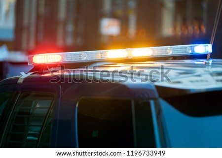 Police car traffic stop with three siren lights simultaneously blinking - red, yellow and blue .