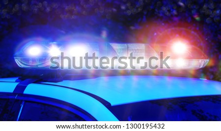Police car with focus on siren lights at night time. Beautiful siren lights activated in full mission activity. Emergency lights flashing on patrol car.