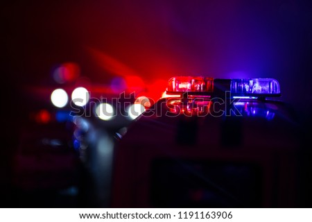 Police cars at night. Police car chasing a car at night with fog background. 911 Emergency response police car speeding to scene of crime. Selective focus #1191163906