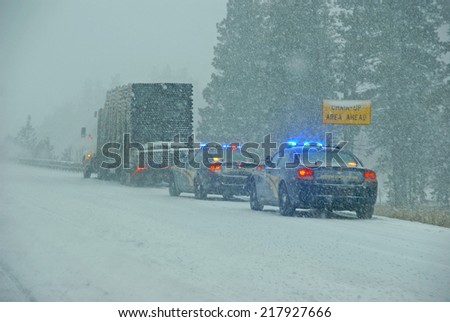 Police cars stop to assist  a large truck during a winter storm  in Eastern Oregon
