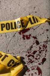 Police cordon tape lies on the ground in a small amount of blood.
