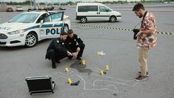 Police crime scene investigation. Two policemen working with evidence while a forensics researcher taking photographs of the body outline.