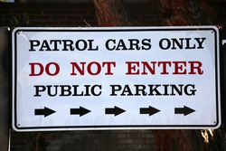 Police Department PATROL CARS ONLY parking sign. A DO NOT ENTER sign at a Police Station.