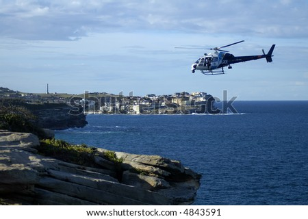 police helicopter flying above rocky coastline, photo taken in Sydney