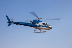 Police helicopter in flight speeding against the blue sky