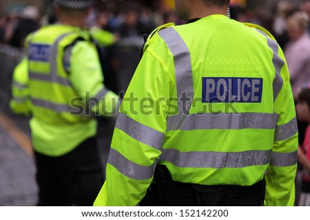 Police in hi-visibility jackets policing crowd control at a UK event