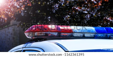 Police lights on car during traffic surveillance on the city road. Flash light on the vehicle of the Emergency Services. Red and blue flashes on the cars of the Patrol specialized unity.