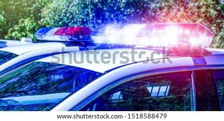 Police lights on car during traffic surveillance on the city road. Flash light on the vehicle of the Emergency Services. Red and blue flashes on the cars of the Patrol specialized unity. Conceptual.