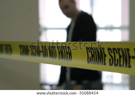 Police line tape and detective in the background - Shutterstock ID 35088454