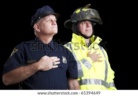 Police officer and fire fighter with their hands over their hearts as they say the Pledge of Allegiance.